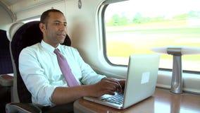 Бизнесмен коммутируя для работы на поезде и используя компьтер-книжку видеоматериал