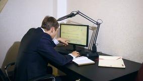 Бизнесмен контролирует изменения в план-графике на валютной бирже, смотря монитор компьютера видеоматериал