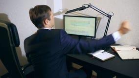 Бизнесмен контролирует изменения в план-графике на валютной бирже, смотря монитор компьютера акции видеоматериалы