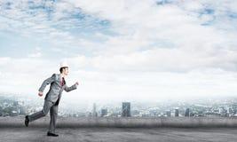 Бизнесмен короля в элегантном костюме бежать на крыше и деловом центре здания на предпосылке Стоковые Фото