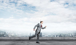Бизнесмен короля в элегантном костюме бежать на крыше и деловом центре здания на предпосылке Стоковое фото RF