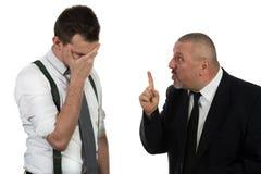 Бизнесмен кричащий и воюя на молодом коллеге Стоковая Фотография