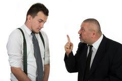 Бизнесмен кричащий и воюя на молодом коллеге Стоковая Фотография RF