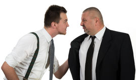 Бизнесмен кричащий и воюя на молодом коллеге Стоковые Изображения RF