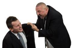 Бизнесмен кричащий и воюя на молодом коллеге Стоковые Изображения