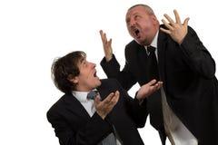 Бизнесмен кричащий и воюя на молодом коллеге Стоковое Изображение