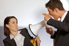 Бизнесмен крича на коммерсантке через мегафон и показывать знак оружия Стоковое фото RF