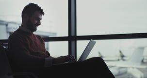 Бизнесмен крупного плана в аэропорте ждать его посадочный талон он работает на его ноутбуке и говорить по его телефону, он сток-видео