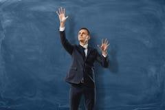 Бизнесмен кладет мнимое buttond на голубую предпосылку классн классного Стоковая Фотография