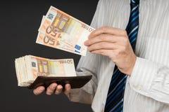 Бизнесмен кладя банкноты в его бумажник Стог денег 50 евро Бизнесмен держит наличные деньги Персона оплачивает в счетах евро Стоковая Фотография RF