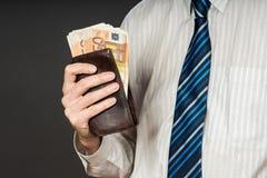Бизнесмен кладя банкноты в его бумажник Стог денег 50 евро Бизнесмен держит наличные деньги Персона оплачивает в счетах евро Стоковое фото RF