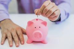 Бизнесмен кладя деньги в изолированную копилку на белой предпосылке Стоковые Изображения RF