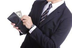 Бизнесмен кладя деньги доллара для оплаты что-то Стоковое фото RF