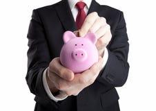 Бизнесмен кладя монетку в изолированную копилку на белой предпосылке Стоковая Фотография RF