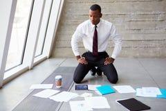 Бизнесмен кладя документы на пол для того чтобы запланировать проект стоковые изображения rf