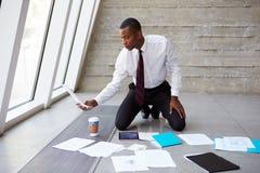 Бизнесмен кладя документы на пол для того чтобы запланировать проект стоковые фотографии rf