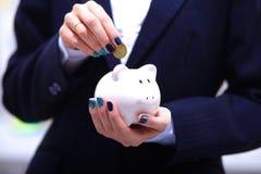 Бизнесмен кладя 100 долларовых банкнот в его Стоковое Изображение RF