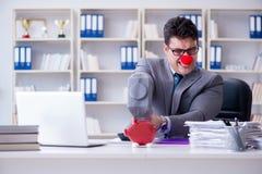 Бизнесмен клоуна с копилкой и молотком Стоковое фото RF