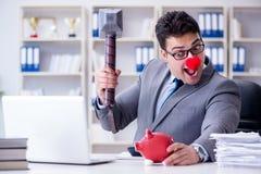 Бизнесмен клоуна с копилкой и молотком Стоковое Изображение RF