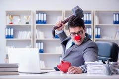 Бизнесмен клоуна с копилкой и молотком Стоковые Изображения
