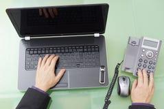 Бизнесмен набирает для поддержки и работает на компьтер-книжке стоковая фотография