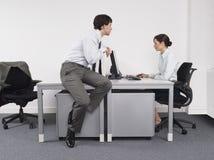 Бизнесмен наблюдая женского коллеги в офисе Стоковое Изображение RF