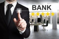 Бизнесмен нажимая банк кнопки сенсорного экрана стоковая фотография