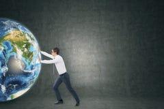 Бизнесмен нажимая глобус около пустого классн классного Стоковые Изображения RF