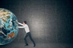 Бизнесмен нажимая глобус около пустого классн классного Стоковое Изображение RF