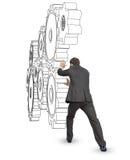 Бизнесмен нажимая колеса cog Стоковая Фотография