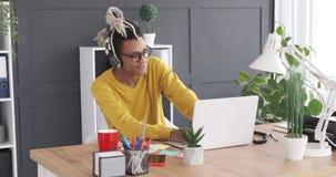 Бизнесмен наслаждаясь музыкой используя наушники и ноутбук офиса сток-видео