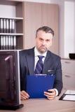Бизнесмен на его столе в офисе смотря папку Стоковые Фотографии RF