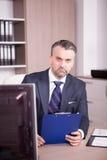 Бизнесмен на его столе в офисе смотря папку Стоковые Изображения RF