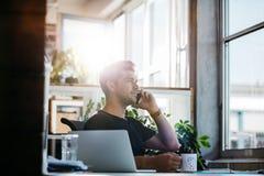 Бизнесмен на его столе говоря на мобильном телефоне Стоковые Изображения