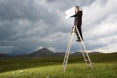 Бизнесмен на лестнице держа пустой знак Стоковая Фотография RF