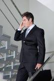 Бизнесмен на звонке идя вниз с лестниц стоковая фотография