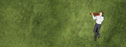 Бизнесмен на зеленой траве стоковые изображения