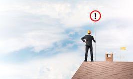 Бизнесмен на знаке дома верхнем показывая с восклицательным знаком Мультимедиа Стоковое Фото