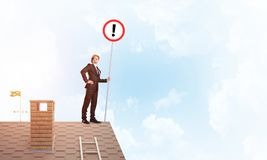 Бизнесмен на знаке дома верхнем показывая с восклицательным знаком Мультимедиа Стоковые Фотографии RF