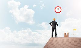 Бизнесмен на знаке дома верхнем показывая с восклицательным знаком Мультимедиа Стоковое Изображение RF