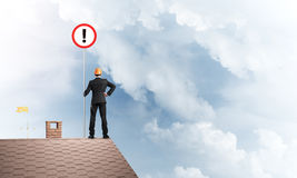 Бизнесмен на знаке дома верхнем показывая с восклицательным знаком смешивание Стоковые Фотографии RF