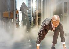 Бизнесмен на линии старта на стрелке сформировал дорогу в улице с пирофакелами Стоковые Фото