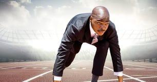 Бизнесмен на линии старта на следе против пирофакелов Стоковое фото RF