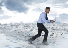 Бизнесмен на компьтер-книжке в море документов под небом заволакивает Стоковое Фото