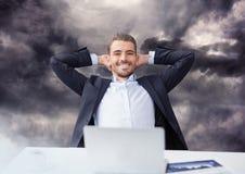 Бизнесмен на компьтер-книжке под темными облаками неба Стоковое Изображение RF