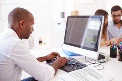 Бизнесмен на компьютере в офисе начинает вверх дело стоковое изображение