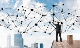 Бизнесмен на крыше дома представляя концепцию сети и соединения Мультимедиа Стоковые Фото