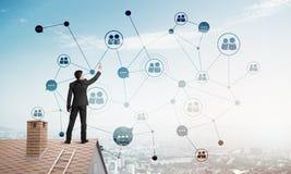 Бизнесмен на крыше дома представляя концепцию сети и соединения Мультимедиа Стоковая Фотография
