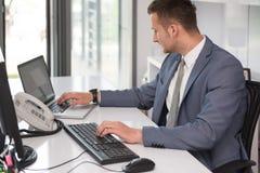 Бизнесмен на проломе с его компьютером Стоковые Фото