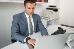 Бизнесмен на проломе с его компьютером Стоковая Фотография